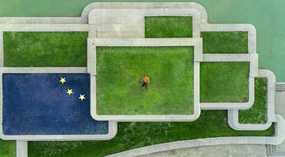 Man laying on intersecting lawns with EU flag
