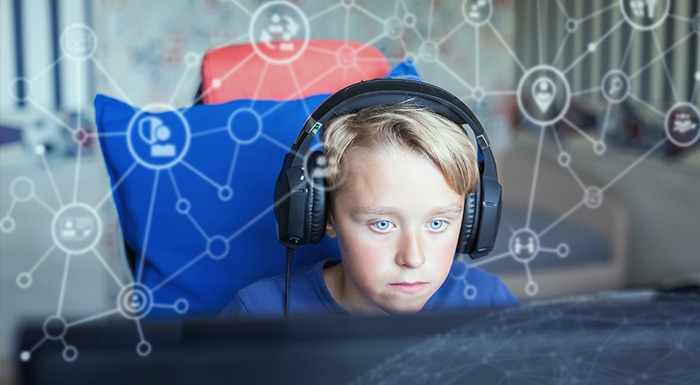 Child using computer with background visualisation of social networks